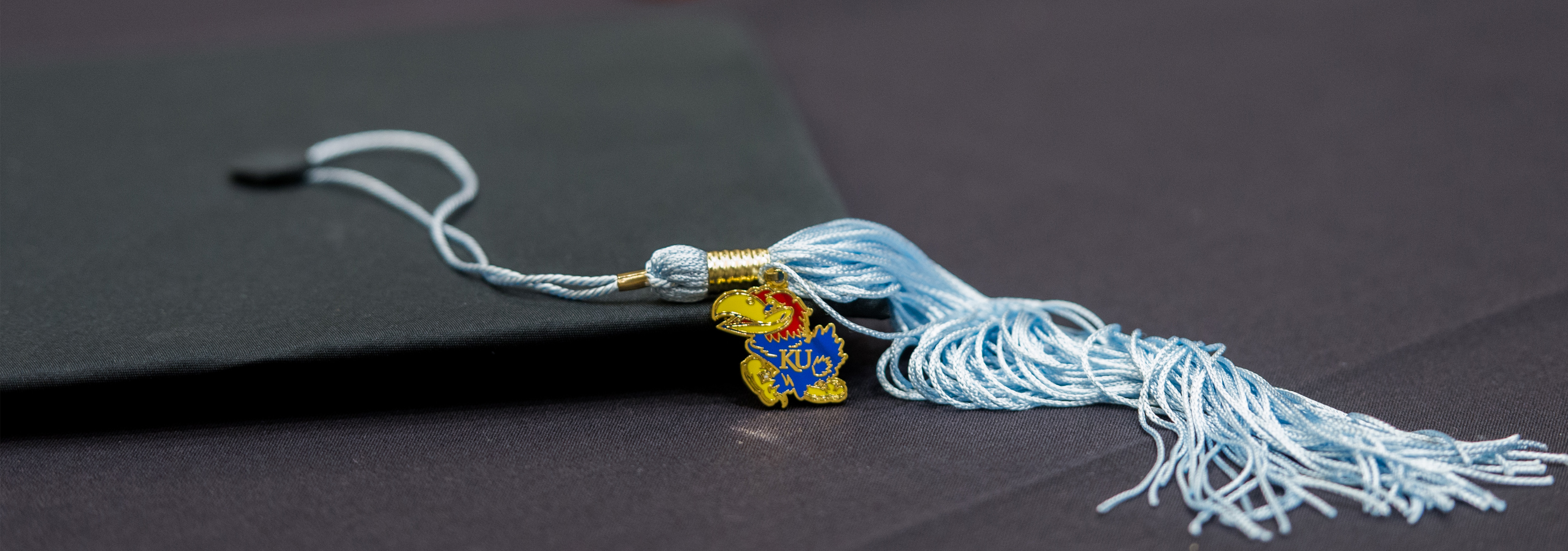 A graduation hat with a Jayhawk on the tassle