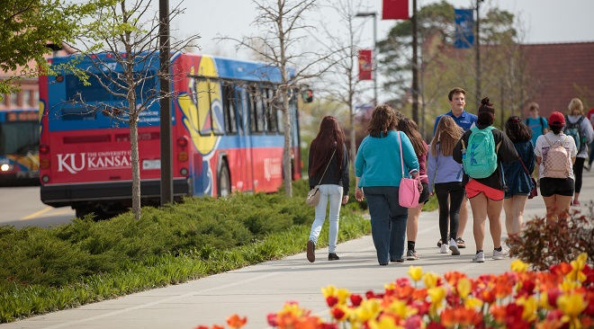 A group of people is getting a tour of KU campus in the spring while a bus passes on the left.